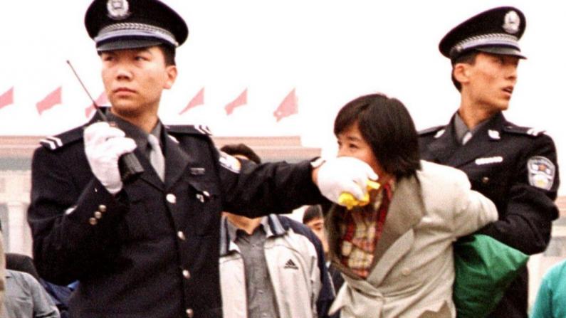 Dos oficiales de policía chinos arrestan a un practicante de Falun Gong en la Plaza de Tiananmen, en Beijing, el 10 de enero de 2000. (Minghui.org)