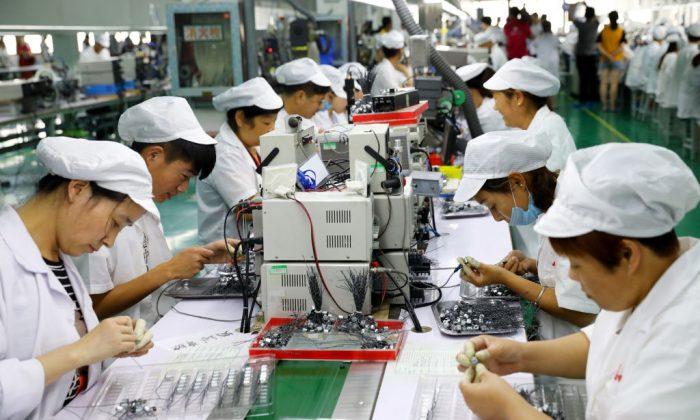 Empleados trabajan en una línea de producción de micromotores en una fábrica de Huaibei, el 23 de junio de 2018. (AFP/Getty Images)