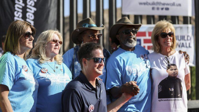 """Brian Kolfage, fundador de """"We Build the Wall"""", con un grupo de familias de ángeles, cuyos hijos fueron asesinados por extranjeros ilegales, frente a la nueva sección de la cerca fronteriza en Sunland Park, Nuevo México, el 30 de mayo de 2019. (Charlotte Cuthbertson/La Gran Época)"""