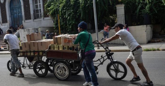 Hombres empujan un triciclo cargado de comestibles, a lo largo de una calle de La Habana, el 5 de abril de 2019. Foto de YAMIL LAGE/AFP/Getty Images.