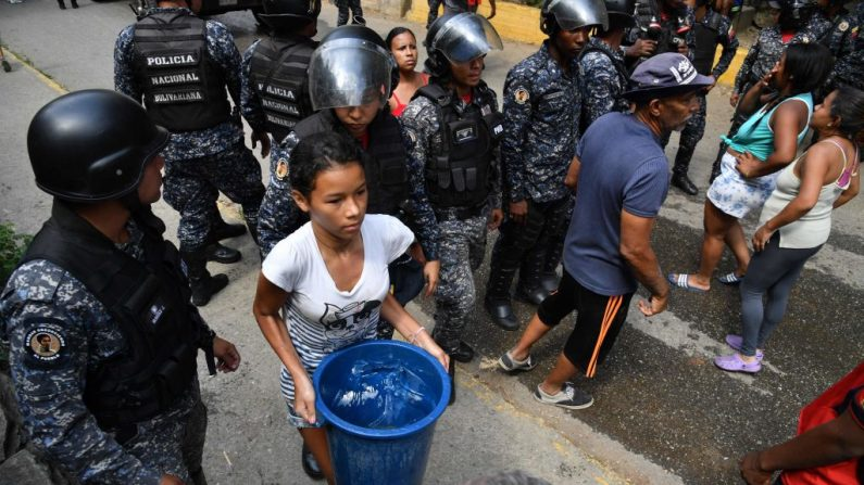 Miembros de la Policía Nacional Bolivariana organizan la distribución de agua potable a los residentes del barrio de San Agustín en Caracas el 11 de marzo de 2019, mientras que un apagón masivo afectaba la Venezuela socialista. (YURI CORTEZ/AFP/Getty Images)