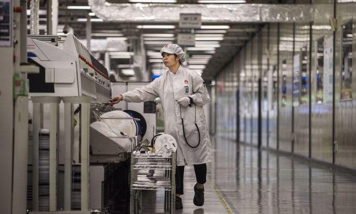 Personal técnico empaca dispositivos de teléfonos inteligentes al final de una línea de producción en una planta de producción de Huawei en Dongguan, cerca de Shenzhen, China, el 11 de abril de 2019. (Kevin Frayer/Getty Images)