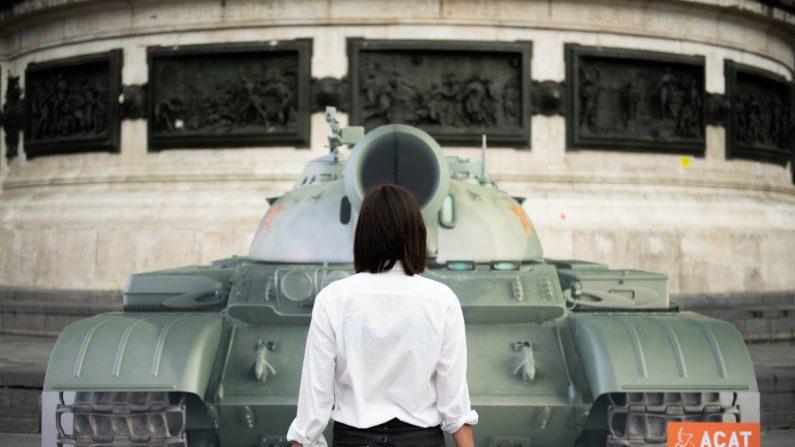 """Una activista se para frente a la imagen de un tanque en París, Francia, replicando la escena donde un desconocido hombre chino, conocido como el """"Hombre del tanque"""", se paró frente a una columna de tanques durante las protestas de la Plaza de Tiananmen de 1989 en Pekín. para conmemorar el 30 aniversario de la masacre de la Plaza de Tiananmen el 4 de junio de 2019. (Créditos: Stringer/AFP/Getty Images)"""