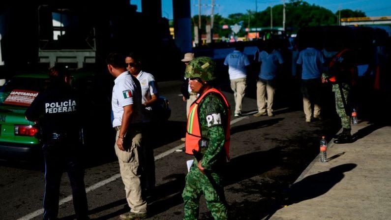 Un oficial de la Policía Militar Mexicana y agentes de inmigración mexicanos esperan en un puesto de control en las afueras de Tapachula, estado de Chiapas, México, el 7 de junio de 2019. (PEDRO PARDO/AFP/Getty Images)