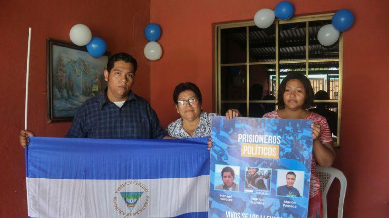 Hansel Vásquez (izq), uno de los 50 presos políticos liberados en virtud de una nueva y controvertida ley que concede amnistía a los manifestantes y policías involucrados en el levantamiento mortal del año pasado contra Daniel Ortega, posa para una foto con su madre (C) y su hermana después de ser liberados, en Managua el 10 de junio de 2019. (MAYNOR VALENZUELA/AFP/Getty Images)