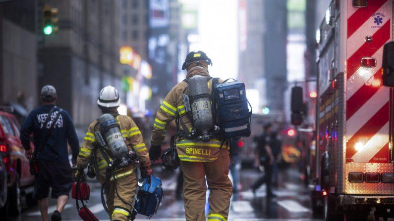Bomberos ayudando luego de que un helicóptero se estrellara en un edificio en el centro de Manhattan en Nueva York el 10 de junio de 2019. (Créditos: Johannes Eisele/AFP/Getty Images)