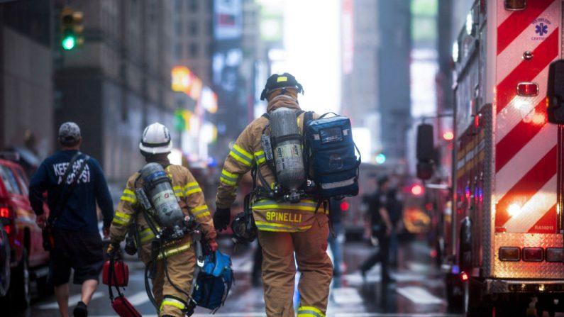 Los bomberos después que un helicóptero se estrelló en la cima de un edificio en el centro de Manhattan en Nueva York el 10 de junio de 2019. (JOHANNES EISELE/AFP/Getty Images)