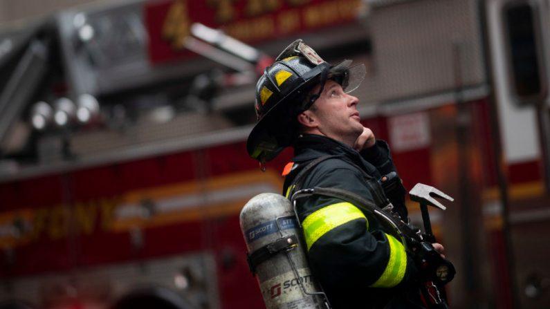 Un bombero mira hacia arriba cerca del edificio donde un helicóptero se estrelló en el centro de Manhattan en Nueva York el 10 de junio de 2019. (JOHANNES EISELE/AFP/Getty Images)