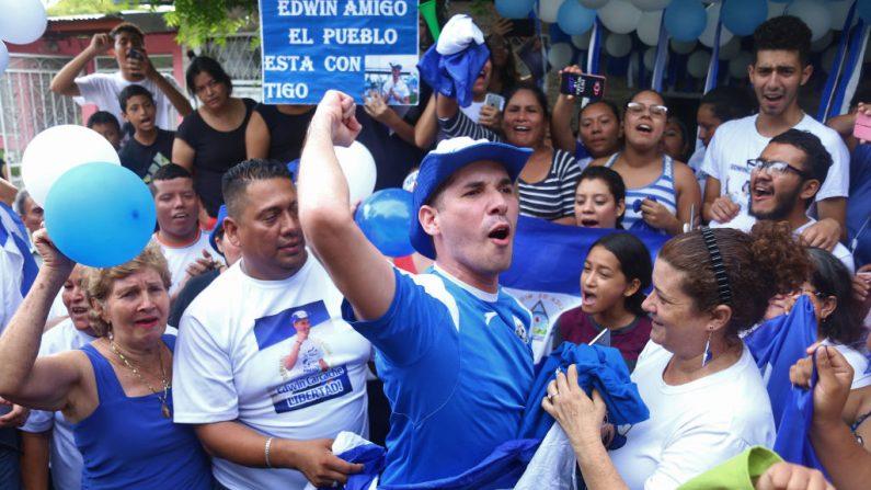 El líder estudiantil Edwin Carcache (C), flanqueado por sus padres, celebra después de haber sido liberado de la prisión, en Managua, el 11 de junio de 2019. (MAYNOR VALENZUELA/AFP/Getty Images)