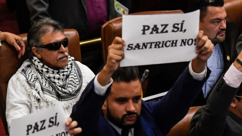 Jesús Santrich (izq.), miembro del partido Fuerza Revolucionaria Alternativa Común (FARC), ocupa su escaño de diputado en el Congreso Nacional de Colombia junto a otros diputados que se manifestaron en contra de su presencia en la cámara baja de Bogotá, el 12 de junio de 2019. (JUAN BARRETO/AFP/Getty Images)