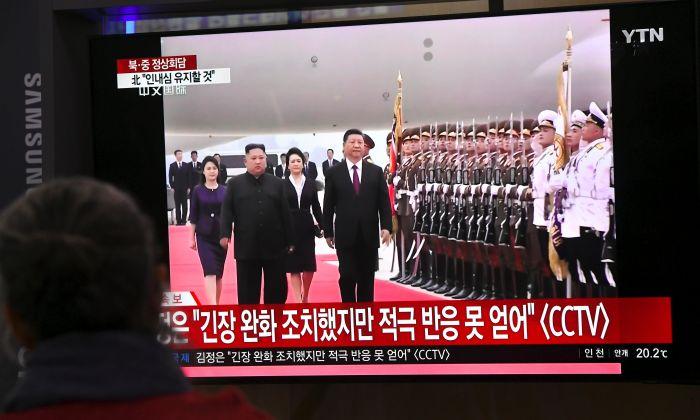 Gente mira las noticias en una pantalla de televisión que muestra al líder norcoreano Kim Jong Un dando la bienvenida al mandatario chino Xi Jinping en el aeropuerto de Pyongyang, el 20 de junio de 2019. (JUNG YEON-JE/AFP/Getty Images)