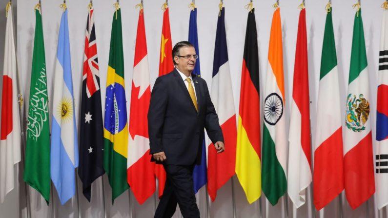 El canciller mexicano Marcelo Ebrard pasa junto a las banderas de los miembros del G20 mientras es recibido por el primer ministro japonés Shinzo Abe en la Cumbre del G20 en Osaka el 28 de junio de 2019. (LUDOVIC MARIN/AFP/Getty Images)