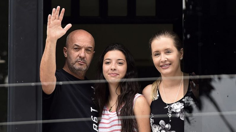 El ex comisario de la policía de Caracas, Ivana Simonovis (izq.), saluda desde la ventana de su casa junto a su hija Ivana (der.) y su esposa Bony Pertinez en Caracas el 20 de septiembre de 2014. Foto de JUAN BARRETO/AFP/Getty Images.