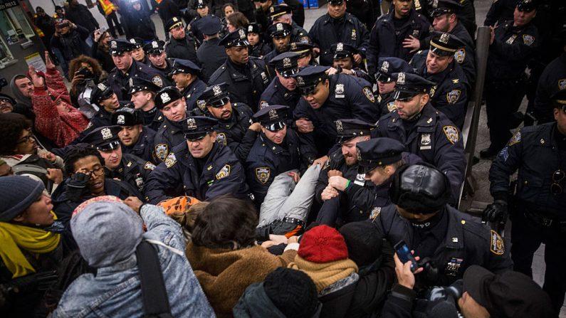 NUEVA YORK, NY - DICIEMBRE 08: Choque entre la polícia y  manifestantes que protestan contra la decisión del Tribunal de Nueva York de no acusar a un oficial de policía involucrado en la muerte de una persona dentro de la estación de metro del Centro Barclays. (Foto de Andrew Burton/Getty Images)