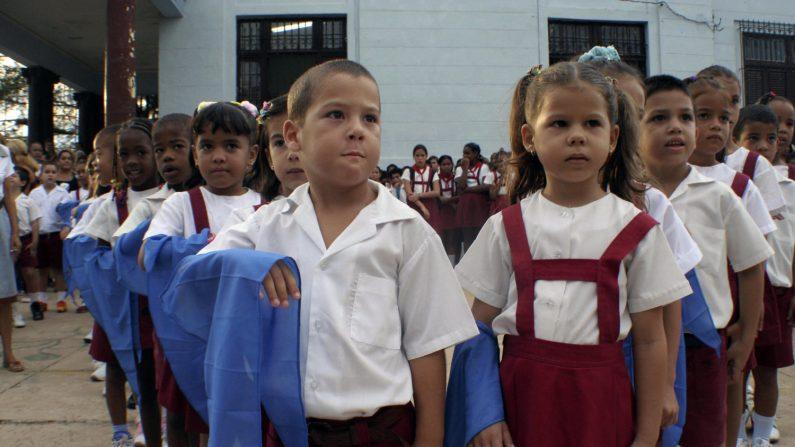 """Un grupo de niños cubanos sostienen sus bufandas durante una ceremonia de iniciación de """"pioneros"""" (pioneros) y afirman el eslogan: """"Pioneros por el comunismo, seremos como el Che"""", en referencia al líder guerrillero Ernesto Che Guevara, el 9 de octubre de 2006. (Créditos: DIANE MAYA/AFP/Getty Images)"""