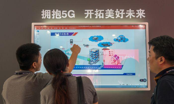 Personas viendo una pantalla que muestra información sobre tecnología 5G durante la Conferencia Mundial Móvil en Shanghai el 27 de junio de 2018. (-/AFP/Getty Images)