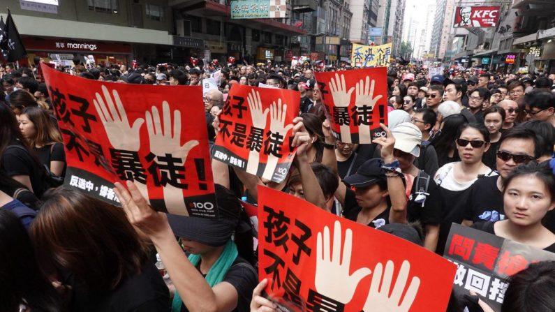 """Manifestantes sostienen carteles chinos que dicen """"Los niños no son alborotadores"""" durante una marcha en Hong Kong el 16 de junio de 2019. (Yu Gang/The Epoch Times)"""
