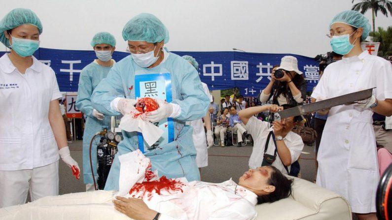 Durante un mitin en el que se unieron miles de practicantes de Falun Dafa en Taipei el 23 de abril de 2006. Cuatro manifestantes actúan en una obra sobre el asesinato de los practicantes de Falun Dafa y la sustracción de sus órganos en campos de concentración, a mano de los comunistas chinos. (Patrick Lin/AFP/Getty Images)