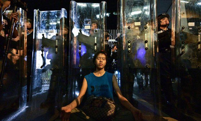 Lam Ka Lo (Centro) medita frente a una fila de policías antidisturbios en guardia con sus escudos frente a la sede del gobierno en Hong Kong a principios del 12 de junio de 2019. (Anthony Wallace/AFP/Getty Images)