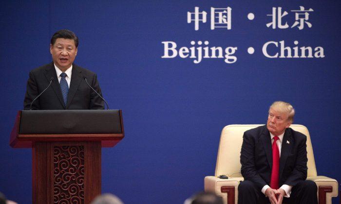 El cabecilla del Partido Comunista Chino, Xi Jinping (izq.), habla junto al presidente Donald Trump durante un evento de líderes empresariales en el Gran Salón del Pueblo en Beijing, el 9 de noviembre de 2017. (NICOLAS ASFOURI/AFP/Getty Images)