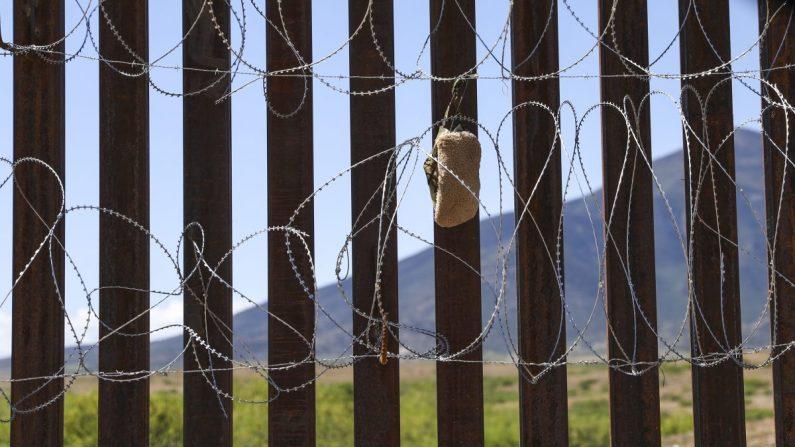 Un zapato de alfombra, generalmente usado por contrabandistas y extranjeros ilegales, queda atrapado en el cable de la valla fronteriza de los Estados Unidos y México cerca de Sierra Vista, Arizona, el 8 de mayo de 2019. (Charlotte Cuthbertson/La Gran Época)