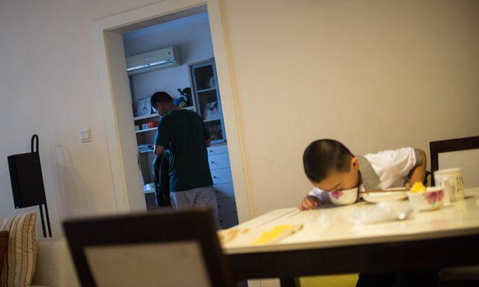Imagen ilustrativa de un niño comiendo con su padre al fondo.  (Johannes Eisele/AFP/Getty Images)