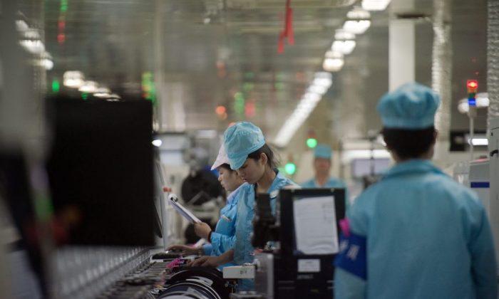 Trabajadores construyen circuitos de componentes de chip para teléfonos inteligentes en una fábrica en la ciudad de Dongguan, provincia de Guangdong, China, el 8 de mayo de 2017. (Nicolas Asforui/AFP/Getty Images)