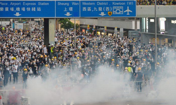 Manifestantes envueltos en gas lacrimógeno durante una protesta contra el proyecto de ley de extradición cerca del Consejo Legislativo de Hong Kong el 12 de junio de 2019. (Song Bilong/La Gran Época)