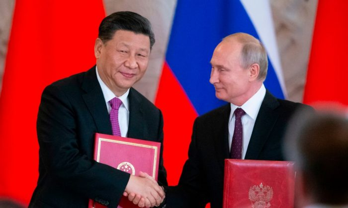 El presidente ruso Vladimir Putin y el mandatario chino Xi Jinping intercambian documentos durante una ceremonia de firma tras sus conversaciones en el Kremlin en Moscú, el 5 de junio de 2019. (Alexander Zemlianichenko/AFP/Getty Images)
