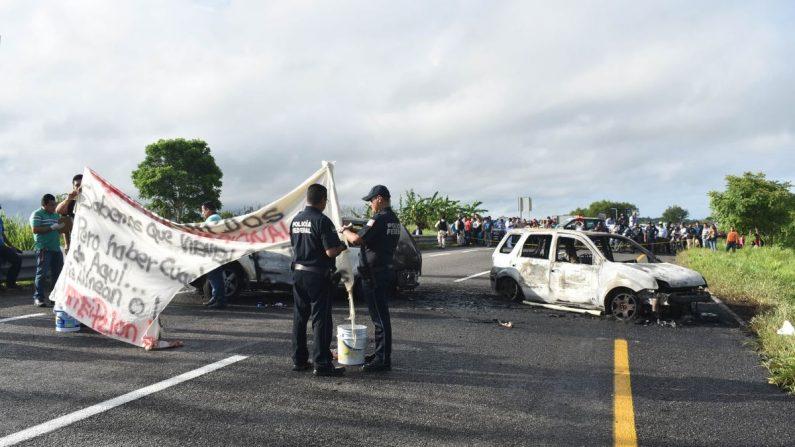 Policías Federales recaban información en el lugar donde presuntos integrantes del crimen organizado bloquearon e incendiaron cinco vehículos, este lunes en Villahermosa (México). EFE/STR