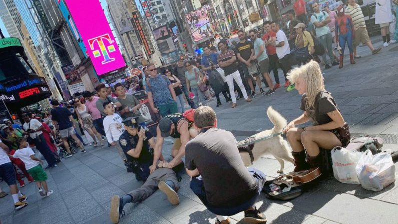 Fotografía cedida por la Policía Nacional del momento en que un agente del cuerpo (en el centro con tirantes), que se encontraba de vacaciones en Nueva York, detiene a un hombre por agredir a un policía estadounidense en la zona de Times Square. EFE/Policía Nacional