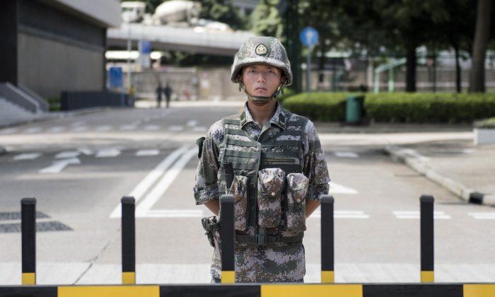 Un soldado del Ejército Popular de Liberación de China (EPL) hace guardia en la entrada del cuartel general de la guarnición del EPL en Hong Kong, el 29 de agosto de 2014. (Alex Ogle/AFP/Getty Images)