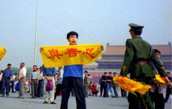 """Un policía chino se acerca a un practicante de Falun Dafa en la Plaza de Tiananmen en Beijing mientras sostiene una pancarta con los caracteres chinos de """"Verdad, Benevolencia y Tolerancia"""", los principios básicos de Falun Dafa. (vía Minghui.org)"""