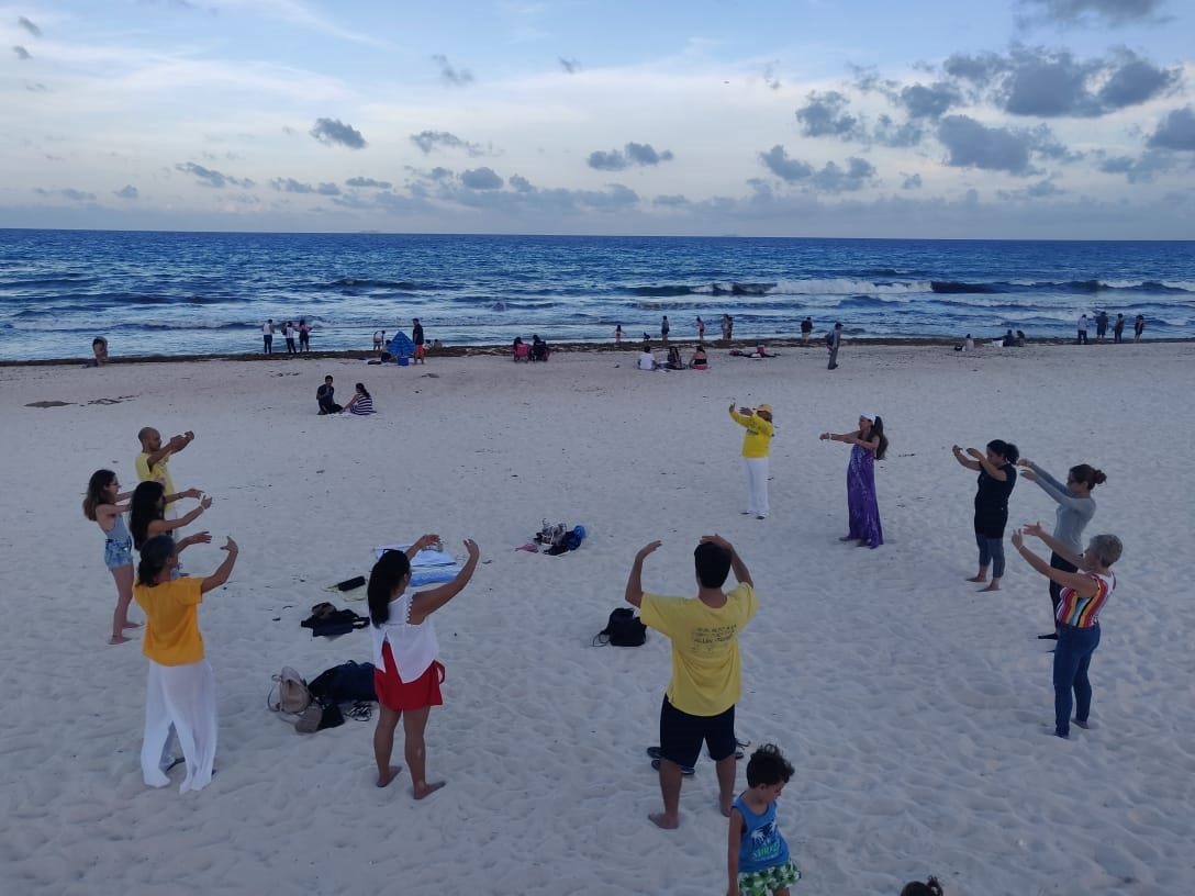 Practicantes de Falun Dafa hacen los ejercicios en una playa de Cancún, en el sureste de México, para dar a conocer los beneficios de la disciplina entre turistas y personas interesadas en mejorar. (Crédito: LGE)