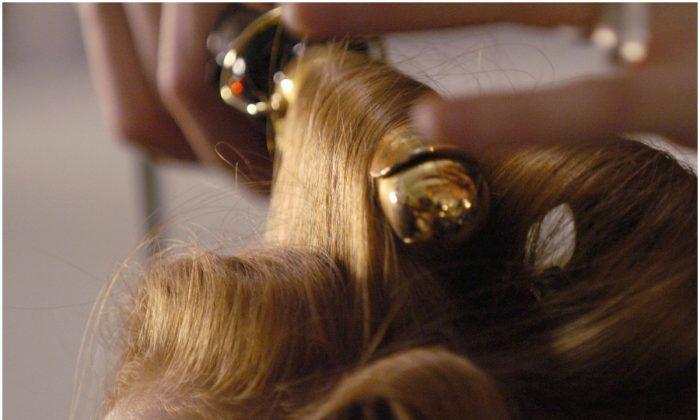 Mujer rizándose el cabello en una foto de archivo. (Stan Honda/AFP/Getty Images)