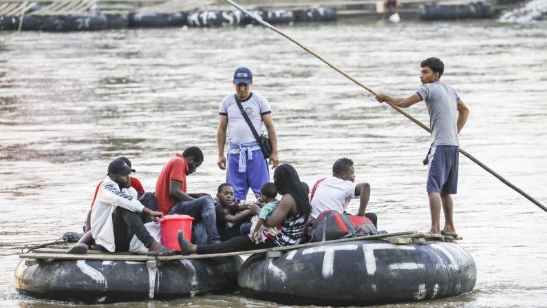 Un grupo de africanos de Angola y el Congo cruzan ilegalmente el río Suchiate en una balsa desde Tecún Umán, Guatemala, a la ciudad de Hidalgo, México, el 27 de junio de 2019. (Charlotte Cuthbertson/La Gran Época)