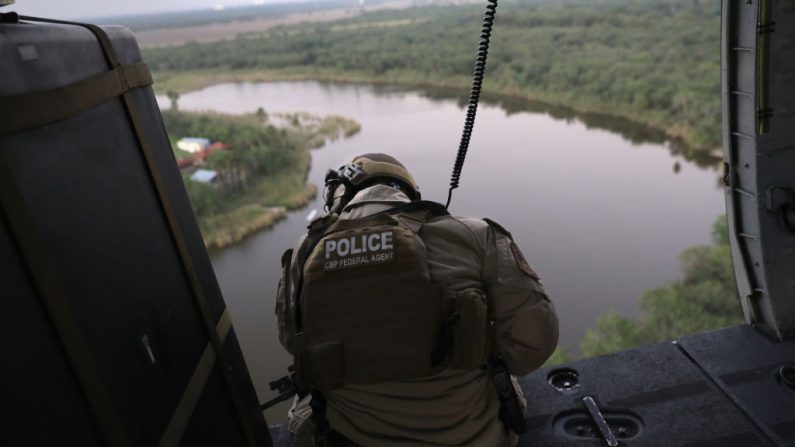 Un agente de Aduanas y Protección Fronteriza de Estados Unidos busca a inmigrantes indocumentados durante una patrulla de helicóptero sobre el Río Grande en la frontera México-Estados Unidos el 6 de noviembre de 2018 en McAllen, Texas. La unidad, que forma parte de Operaciones Aéreas y de Marines de Estados Unidos, coordina con agentes de la Patrulla Fronteriza de Estados Unidos en el terreno para detectar y detener a los inmigrantes indocumentados y a los contrabandistas de drogas que han cruzado el río desde México.  (John Moore/Getty Images)