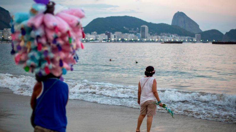 Una mujer observa el océano mientras un vendedor de caramelos pasa en la playa de Copacabana en Río de Janeiro, Brasil, el 31 de diciembre de 2018. (DANIEL RAMALHO/AFP/Getty Images)