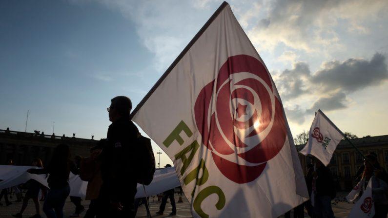 La gente sostiene banderas del partido Fuerza Revolucionaria Alternativa Común (FARC) durante una protesta contra una reforma propuesta por el gobierno para la Jurisdicción Especial para la Paz (JEP) en Bogotá, el 13 de marzo de 2019. (RAUL ARBOLEDA/AFP/Getty Images)