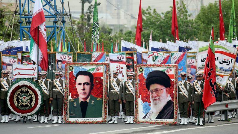 Los soldados iraníes sostienen carteles del líder supremo iraní Ayatollah Ali Khamenei (D) y ex jefe de personal del ejército iraní Sepahbod Mohammad-Vali Gharani (I) mientras marchan durante un desfile militar en el día anual del ejército en Teherán. el 18 de abril de 2019. (Stringer/AFP/Getty Images)