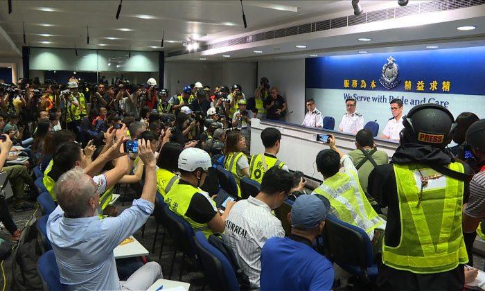 Periodistas de Hong Kong se visten con chaquetas y cascos de alta visibilidad ante la presencia policial para protestar contra el uso excesivo de la fuerza en su contra durante los enfrentamientos del 12 de junio entre la policía y los manifestantes producido por un controvertido proyecto de ley de extradición, en Hong Kong, el 13 de junio de 2019. (AFPTV TEAM/AFP/Getty Images)