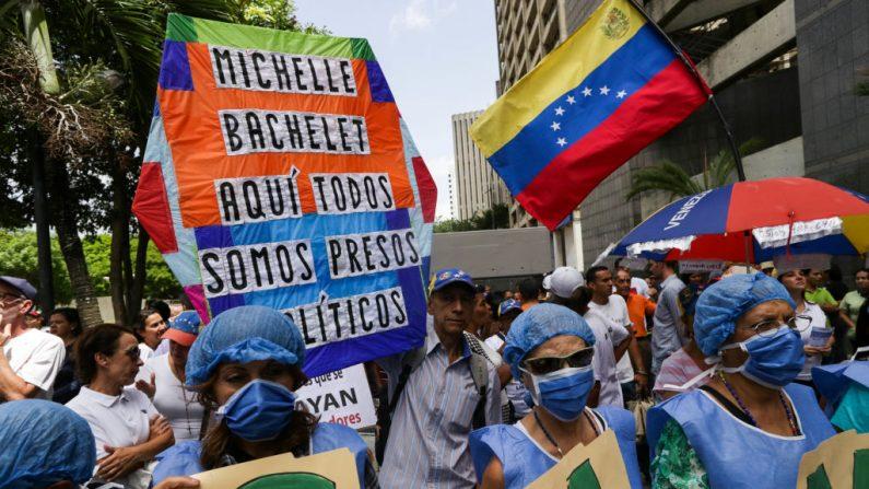 """Venezolanos sostienen un cartel que dice """"Michelle Bachelet, aquí todos somos presos políticos"""" mientras se manifiestan frente a la sede del Programa de las Naciones Unidas para el Desarrollo durante la visita de la Alta Comisionada de las Naciones Unidas para los Derechos Humanos, Michelle Bachelet, en Caracas, el 21 de junio de 2019. (CRISTIAN HERNANDEZ/AFP/Getty Images)"""