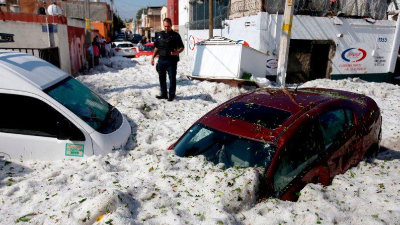Un policía junto a vehículos enterrados en granizo en la zona este de Guadalajara, estado de Jalisco, México, el 30 de junio de 2019. La acumulación de granizo en las calles de Guadalajara enterró vehículos y dañó viviendas. (ULISES RUIZ/AFP/Getty Images)