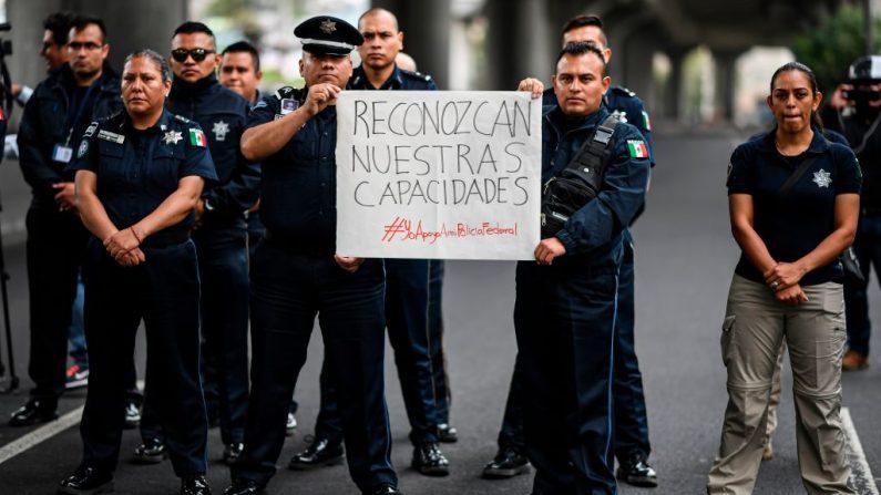 Miembros de la Policía Federal bloquean el Anillo Periférico frente a la sede de la Policía Federal en la Ciudad de México el 3 de julio de 2019 para protestar contra la anexión de la fuerza a la recién formada Guardia Nacional. (RONALDO SCHEMIDT/AFP/Getty Images)