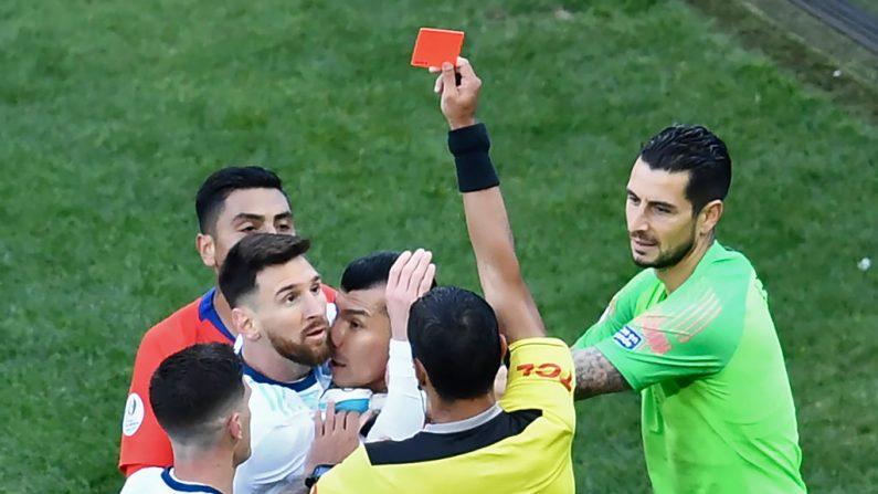 El árbitro paraguayo Mario Díaz de Vivar le muestra la tarjeta roja al argentino Lionel Messi y al chileno Gary Medel, tras un encuentro físico durante el partido por el tercer lugar en el torneo de fútbol de la Copa América en el Corinthians Arena de Sao Paulo, Brasil, el 6 de julio de 2019. (EVARISTO SA / AFP / Getty Images)