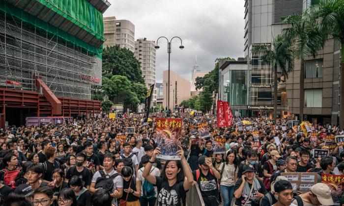Manifestantes sostienen carteles y cantan lemas mientras forman parte de una manifestación en la calle, el 7 de julio de 2019 en Hong Kong, China. (Anthony Kwan/Getty Images)