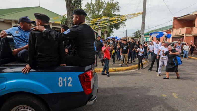La policía antidisturbios es transportada durante una protesta antigubernamental después de una misa en memoria de las personas asesinadas hace un año en protestas contra Daniel Ortega en Jinotepe, Nicaragua, el 8 de julio de 2019. (INTI OCON/AFP/Getty Images)