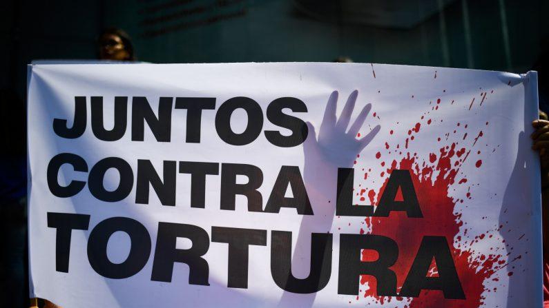 """Un manifestante sostiene un cartel que dice """"Juntos contra la tortura"""" durante una protesta contra el gobierno venezolano frente a la oficina del Programa de las Naciones Unidas para el Desarrollo (PNUD) en Caracas el 15 de julio de 2019. (Federico Parra/AFP/Getty Images)"""