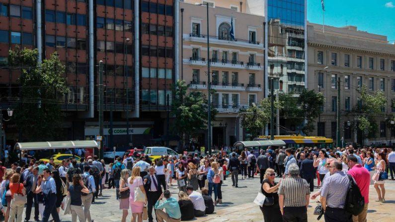 La gente está de pie fuera de los edificios en el centro de Atenas después del terremoto del 19 de julio de 2019. (Eurokinissi/AFP/Getty Images)
