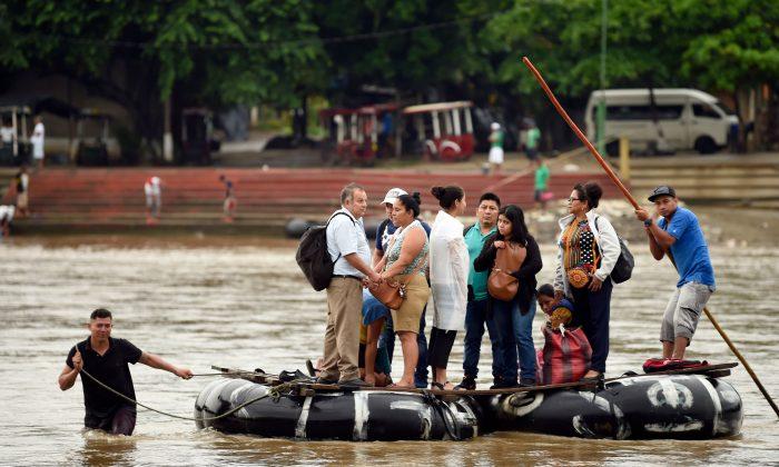 Migrantes guatemaltecos usan una balsa improvisada para cruzar ilegalmente el río Suchiate desde Tecun Uman en Guatemala hasta Ciudad Hidalgo en el estado de Chiapas, México, el 22 de julio de 2019. (ALFREDO ESTRELLA/AFP/Getty Images)